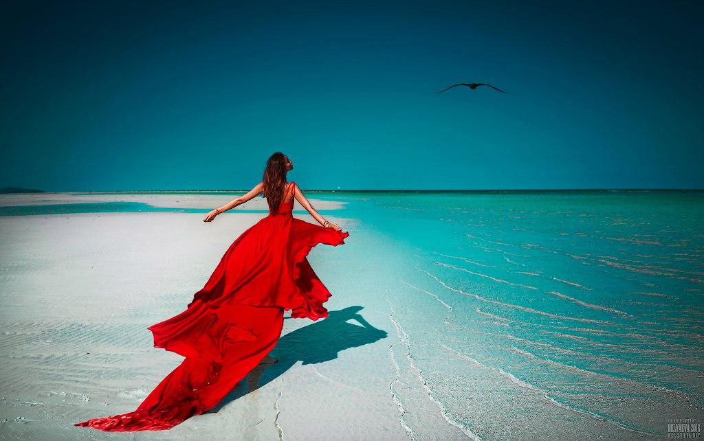 Девушка в красном платье стоит у берега моря, фотограф Светлана Беляева