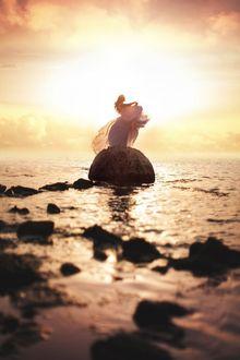 Фото Девушка стоит на камне в окружении воды, на фоне заката