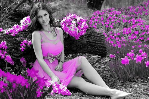 Фото Девушка в розовом сарафане сидит на земле в окружении розовых нарциссов, черно-белое фото с цветными элементами