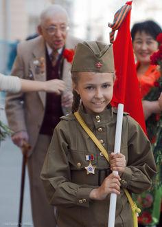 Фото Девочка в военной форме несет флаг СССР с георгиевской ленточкой, на заднем плане идут ветераны ВОВ