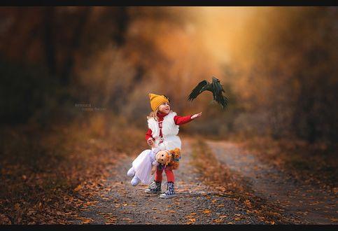 Фото Девочка с куклой стоит на усыпанной осенней листвой дороге, протягивая руку вороне, фотограф Константин Жостег