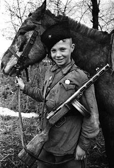 Фото Мальчик в кубанке со звездой, с автоматом и орденом на груди держит лошадь под уздцы, сын полка