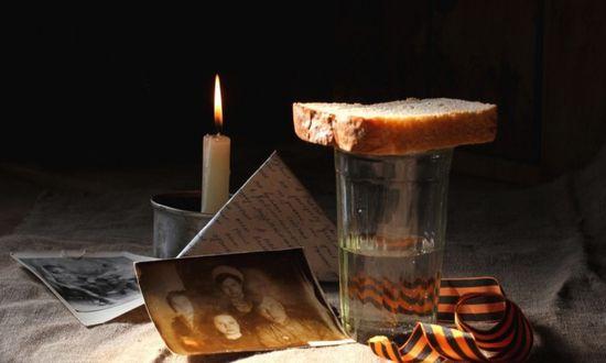 Фото В свете свечи старые фотографии, фронтовое письмо-треугольник, кусок хлеба на стакане с водкой и Георгиевская ленточка