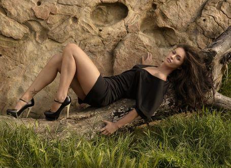 Фото Красивая брюнетка в черном платье и туфлях, разметав волосы, лежит на стволе старого высохшего дерева на фоне скалы
