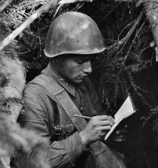 Фото Мужчина пишет письмо сидя в окопе