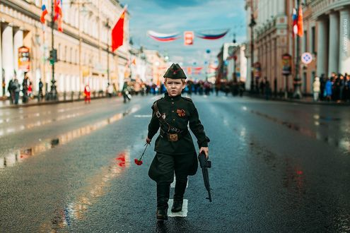 Фото Мальчик в военной форме и с гвоздикой шагает по улице города, фотограф Иван Проскурин