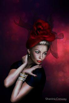 Фото Девушка в красной шляпе с вуалью держит сложив на себе руки, на одной руке браслет, by SHANINA CONWAY