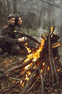 Фото Мужчина с девушкой в военной форме сидят в лесу у костра, by Pshenina Angelika