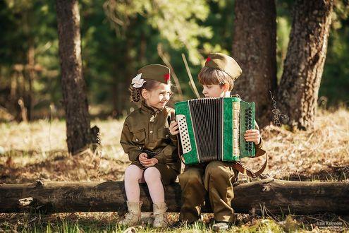 Фото Мальчик и девочка в военной форме, мальчик играет девочке на баяне, фотограф Ирина Крайнова