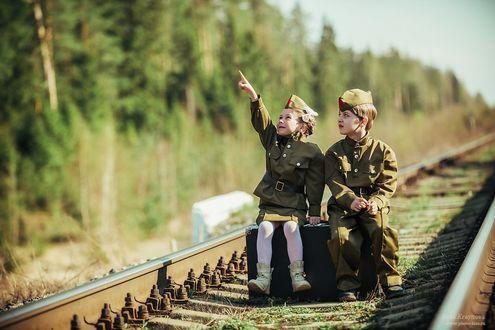 Фото Мальчик и девочка в военной форме сидят на чемодане у железной дороги, фотограф Ирина Крайнова