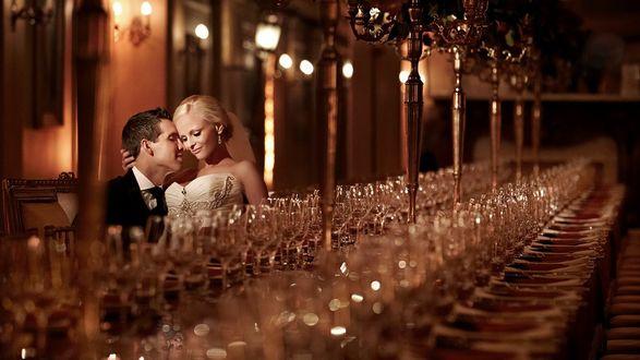 Фото Влюбленная пара стоит посреди зала возле длинного стола, заставленного фужерами, Jerry Ghionis