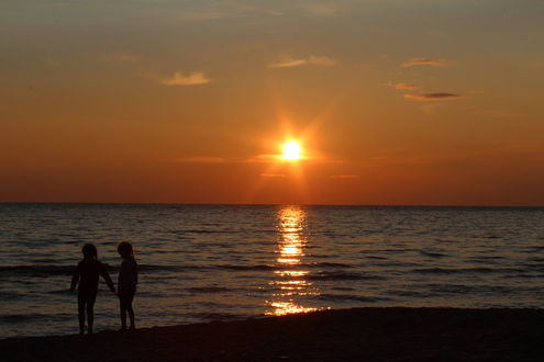 Фото На побережье Рижского залива дети любуются закатом солнца