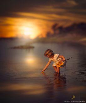 Фото Девочка с подсолнухами в руках стоит в воде на фоне заката, by Jake Olson