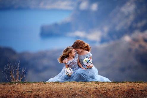 Фото Девушка с дочкой сидят в одинаковых платьях с букетами цветов на фоне залива, фотограф Илья Двояковский