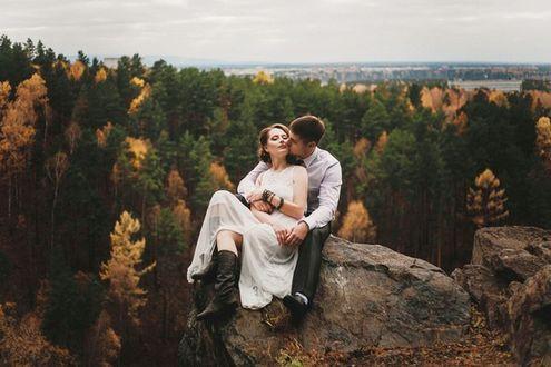 Фото Мужчина целует девушку сидя на вершине горы, на фоне леса, фотограф Лидия Белошапкина