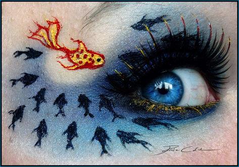 Фото Девушка с темным макияжем, тенями нарисованы рыбы вокруг глаза: одна золотая и множество маленьких черных рыбешек
