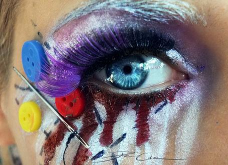 Фото Девушка с необычным мейк-апом, с пуговицами и иглой возле глаза, фиолетовой тушью и красными подтеками