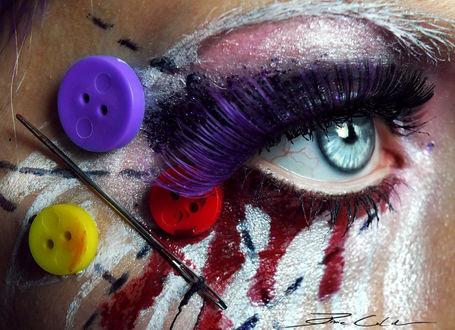 Фото Необычный макияж глаз у девушки, с использованием иголки и пуговиц, с красным подтеком под глазом и фиолетовой тушью