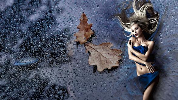 Фото Красивая девушка лежит на поверхности из капель