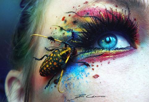 Фото Девушка с ярким цветным макияжем смотрит вверх, на уголке ее глаза желто-черный жук