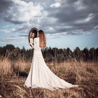 Фото Девушка в белом платье стоит с зеркалом