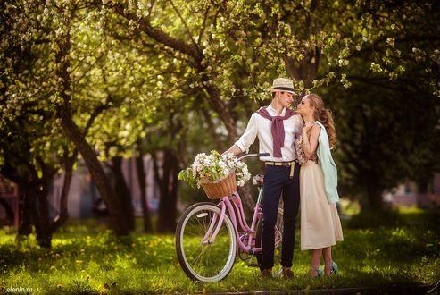 Фото Мужчина с девушкой стоят с велосипедом около цветущего дерева, фотограф Лена Смирнова