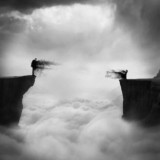 Фото Парень и девушка стоят на краю обрывов, утопающих в облаках, друг напротив друга