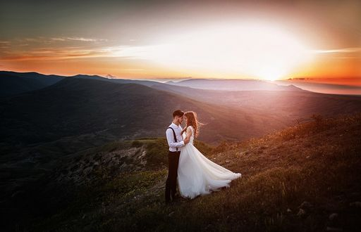 Фото Мужчина с девушкой стоят в горах обнимаясь, на фоне тумана и захода солнца, фотограф Николай Харламов