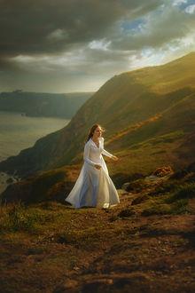 Фото Девушка в длинном белом платье стоит на фоне природы, by TJ Drysdale