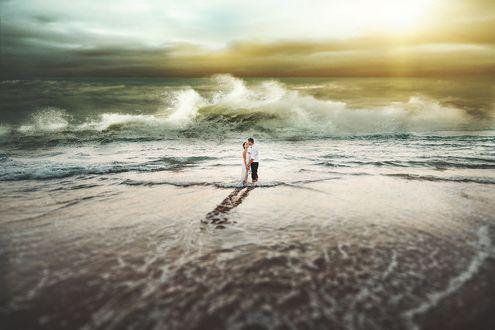 Фото Мужчина с девушкой стоят на берегу моря и целуются