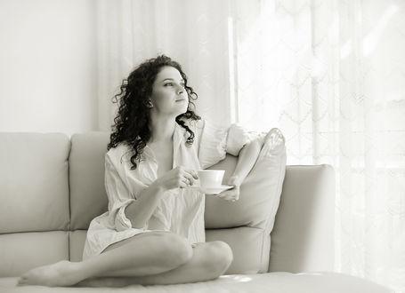 Фото Красивая девушка с распущенными волосами в одной рубашке сидит на диване, поджав ножки, в руках у нее чайная пара