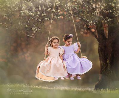 Фото Две девочки катаются на качели, которая висит на ветке цветущего дерева, by Lilia Alvarado