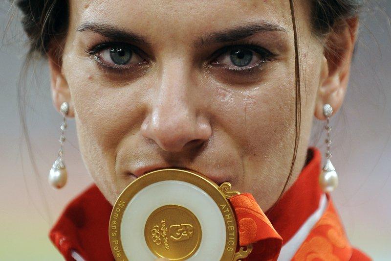 Фото Легкоатлетка Елена Исинбаева со слезами на глазах целует золотую Олимпийскую медаль