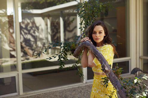 Фото Актриса Emilia Clarke / Эмилия Кларк, известная по роли Dayeneris Targaryen / Дайенерис Таргариен держится за небольшое изогнутое дерево