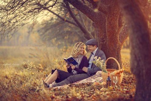 Фото Под деревом на поляне сидит пара: девушка со светлыми волосами, с улыбкой на лице держит в руках книгу, и мужчина в кепке и сером костюме держит девушку за руку, рядом стоит корзинка для пикника, фотограф Ирина Джуль