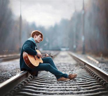 Фото Парень с гитарой сидит на рельсе железнодорожного полотна, фотограф Ирина Джуль
