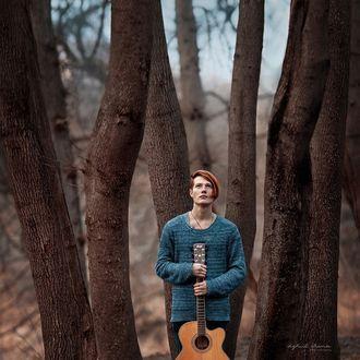 Фото Рыжеволосый парень с длинной челкой, зачесанной на бок, в синем свитере, с гитарой в руках стоит среди деревьев и смотрит вверх, фотограф Ирина Джуль