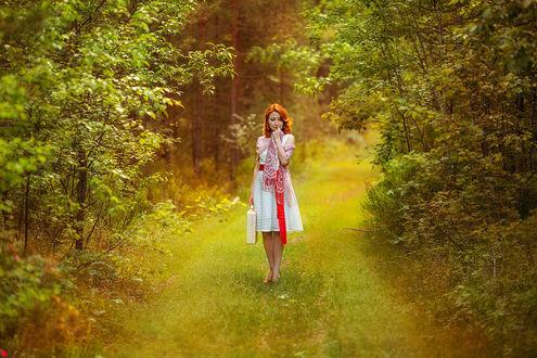 Фото Рыжеволосая девушка в белом платье с красным поясом с белым кейсом в руке идет по лесной дороге, фотограф Ежъ Осипов