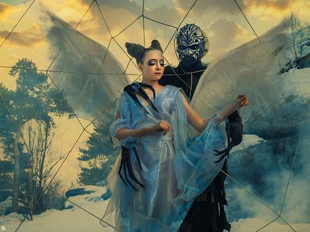 Фото Девушку с белыми крыльями бабочки, с волосами собранными в причудливую прическу, одетую в белое платье, обнимает человек-паук, на фоне деревьев и неба с облаками, фотограф Ежъ Осипов