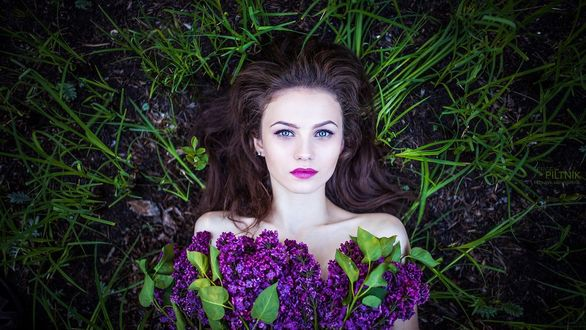 Фото Девушка с темными длинными волосами, голубыми глазами лежит на земле среди травы с букетом сирени, фотограф Сергей Пилтник