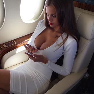 Фото Модель Виктория Одинцова в белом платье сидит в салоне самолета, держа в руках телефон