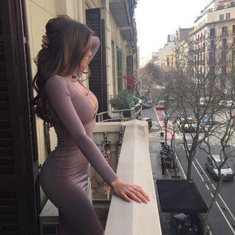 Фото Модель Виктория Одинцова в сиреневом платье стоит на балконе, глядя на уличную суету
