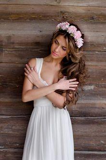 Фото Девушка в венке из цветов стоит у стены