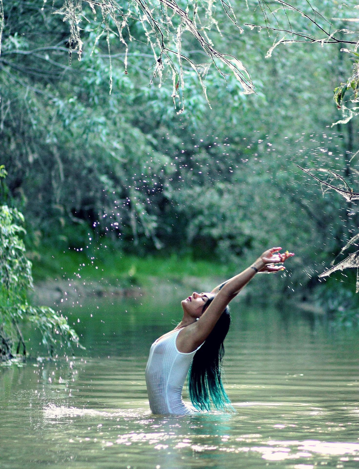 Фото Девушка поднимает тучу брызг, купаясь в лесной речушке, на фоне зеленой листвы