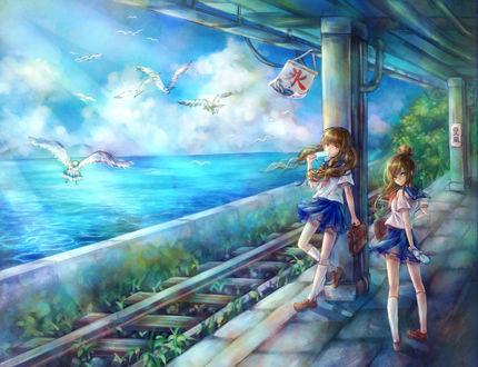 Фото Две школьницы стоят на железнодорожном перроне с которого открывается красивый вид на море, by tandolcedeco