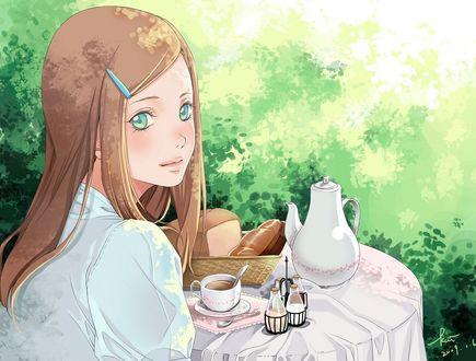 Фото Рыжеволосая девушка сидит за столом на фоне зеленых листьев