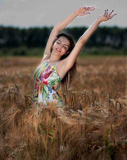 Фото Девушка в цветастом платье, вскинув руки, радуется жизни на ржаном поле