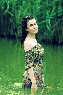 Фото Девушка в легком платье, стоящая по бедра в воде, на фоне стены зеленых деревьев