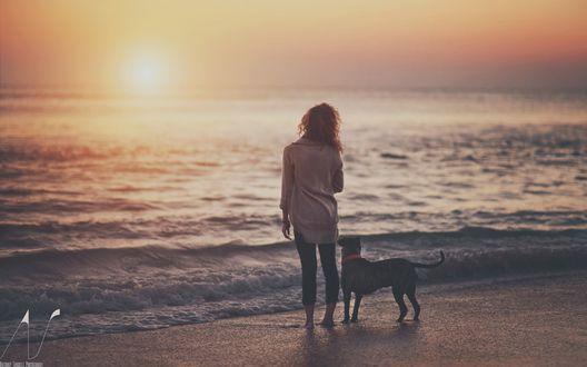 Фото Девушка и собака любуются закатом солнца на море