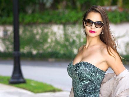 Фото Женщина в облегающем платье и темных очках сбросила с плеч легкую курточку, городская улица, лето